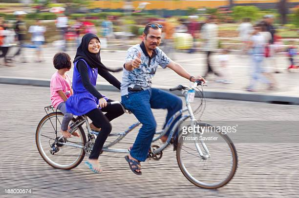 Father and daughters riding a tandem bicycle in Merdeka Square. This was the Eid Holiday , and lots of families with kids enjoyed the sunny day in...