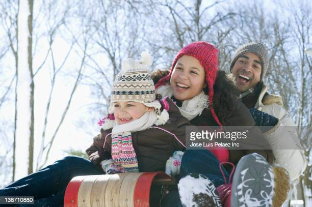 father and daughters sledding down snow covered hill - tobogganing stock pictures, royalty-free photos & images