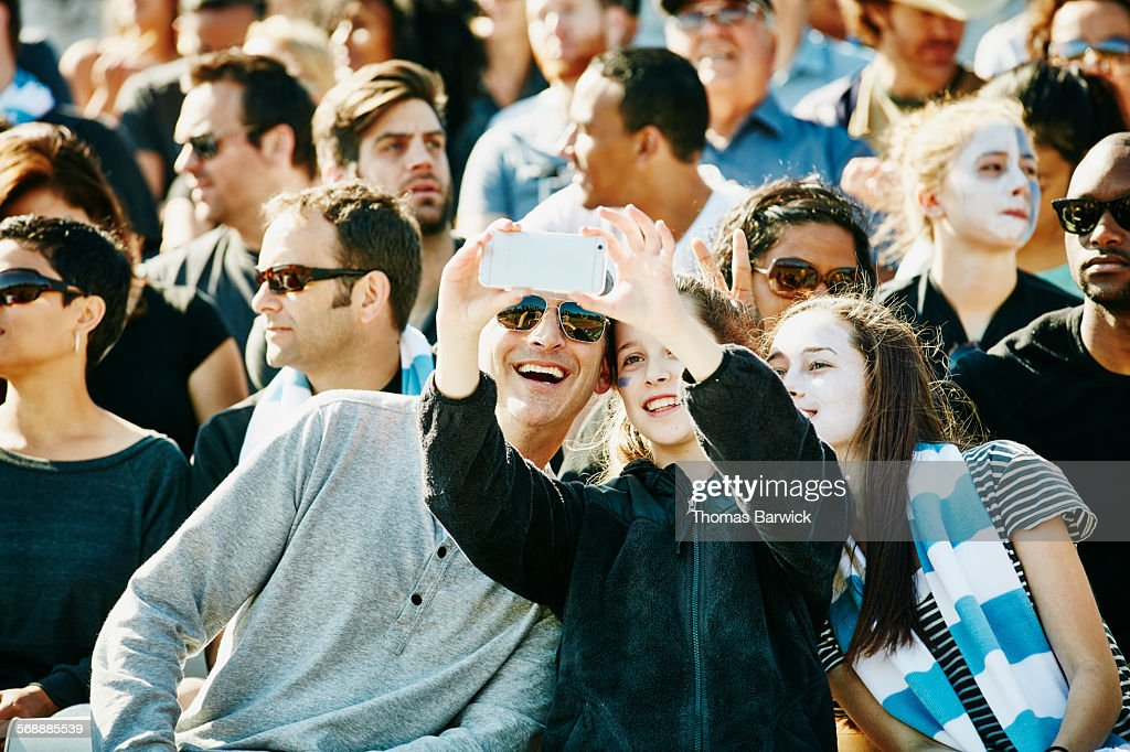 Father and daughters taking selfie in stadium : Stock Photo
