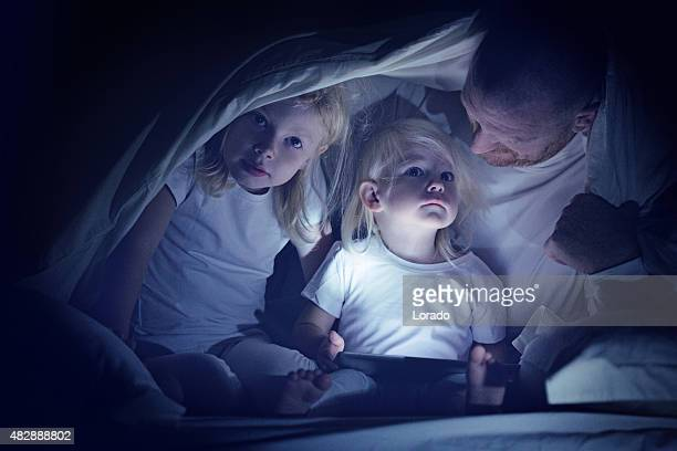 father and daughters using a tablet device - daughters of darkness stock pictures, royalty-free photos & images