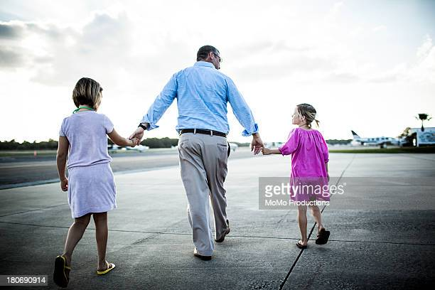 Father and daughters walking onto private airstrip