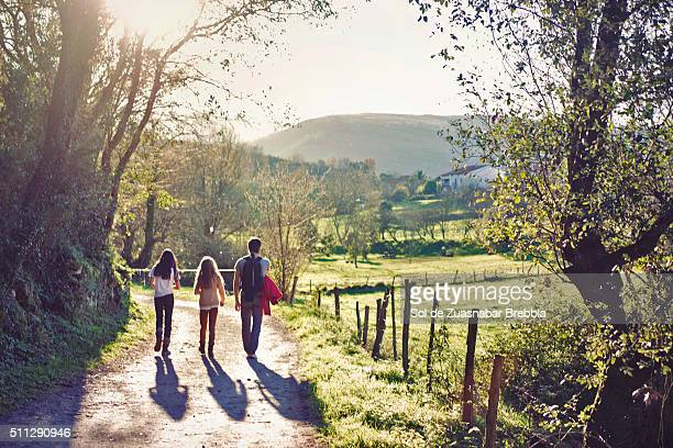 Father and daughters walking together through the countryside