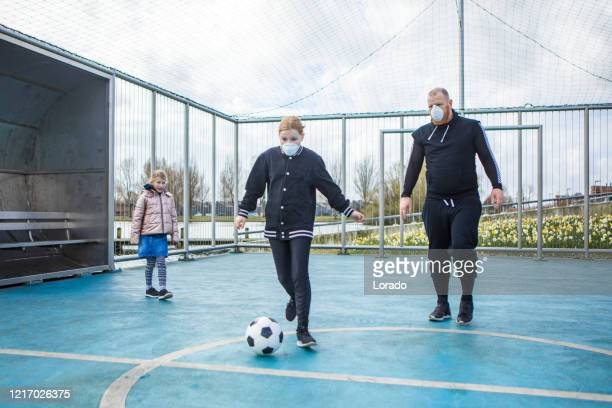 father and daughters wearing face masks whilst playing football - football face mask stock pictures, royalty-free photos & images