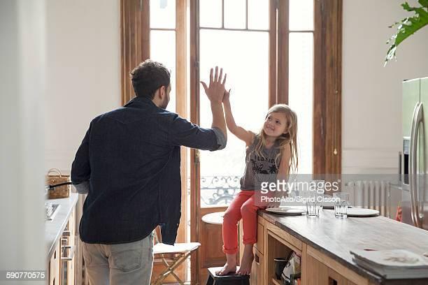 father and daugther high-five - haushaltsaufgabe stock-fotos und bilder
