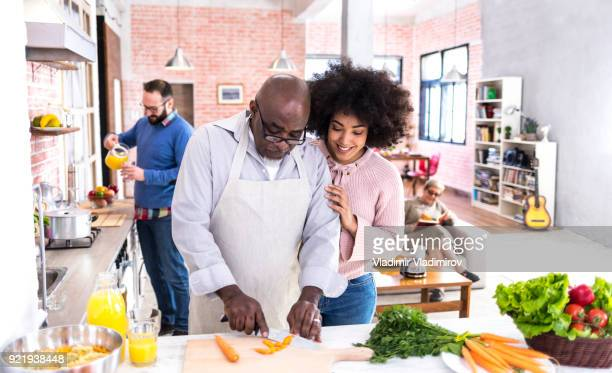 father and daugther making salad at home - black family dinner stock photos and pictures