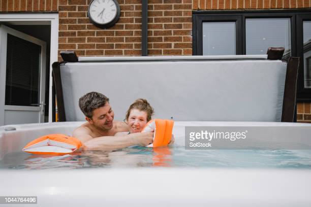 father and disabled daughter in hydrotherapy pool - als stock photos and pictures