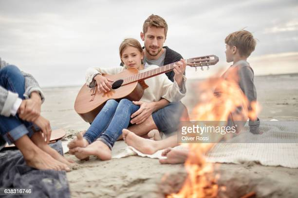 Father and family playing guitar on the beach at campfire