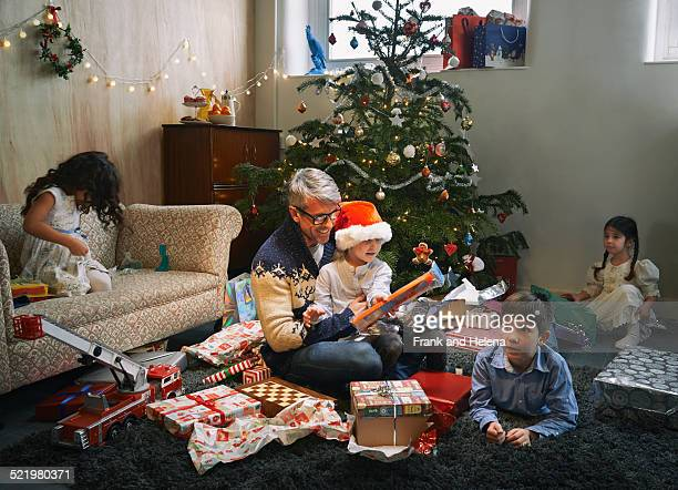 father and four children opening christmas gifts in sitting room - opening stock photos and pictures
