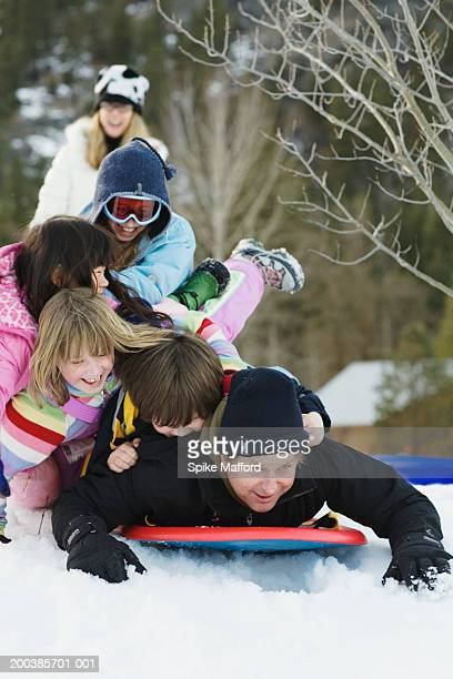 Father and four children (7-10) piled on sled in snow, laughing