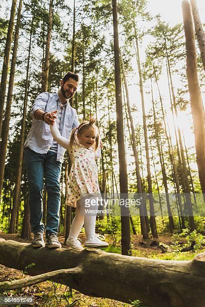 Father and girl balancing on log