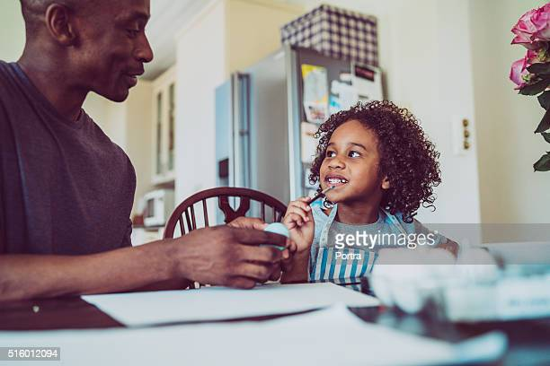 father and girl painting easter egg at home - african american easter stock photos and pictures