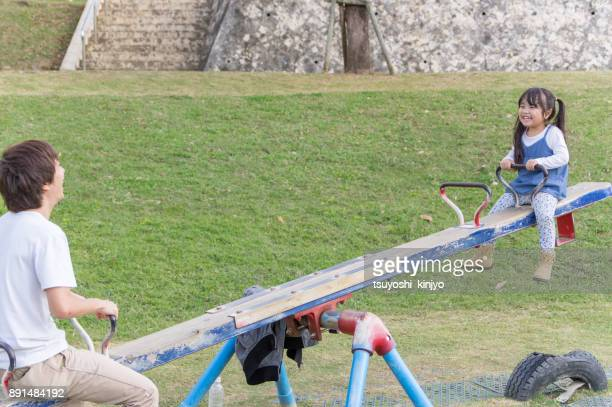 father and girl playing in the park - seesaw stock pictures, royalty-free photos & images