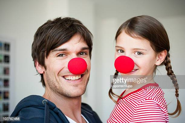 father and girl wearing red noses - clown's nose stock photos and pictures