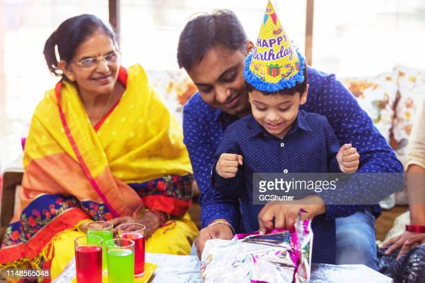 father and grand mother celebrating kid's birthday at home - mid adult stock pictures, royalty-free photos & images