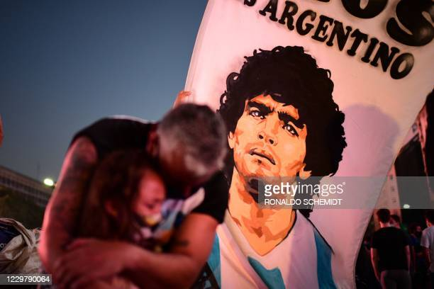 TOPSHOT A father and her daughter fans of Argentinian football legend Diego Maradona mourn as they gather by the Obelisk to pay homage on the day of...