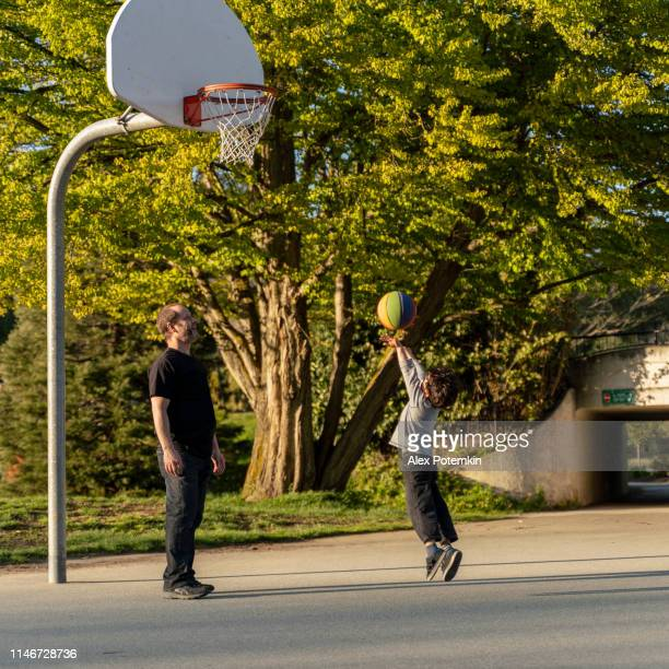 father and his 7-years-old son playing basketball in the stanley park, vancouver, canada - 6 7 years stock pictures, royalty-free photos & images