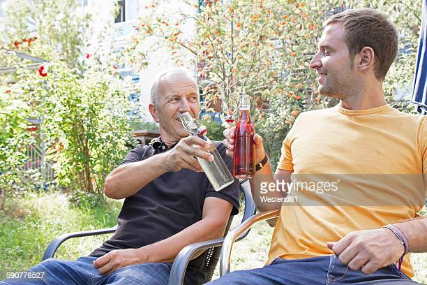 Father and his adult son sitting in the garden toasting with beverages