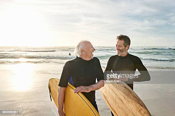 Father and his adult son surfing