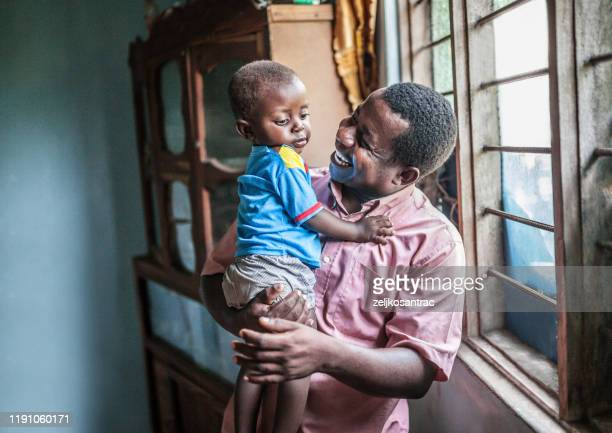 a father and his baby boy looking at a laptop - east africa stock pictures, royalty-free photos & images