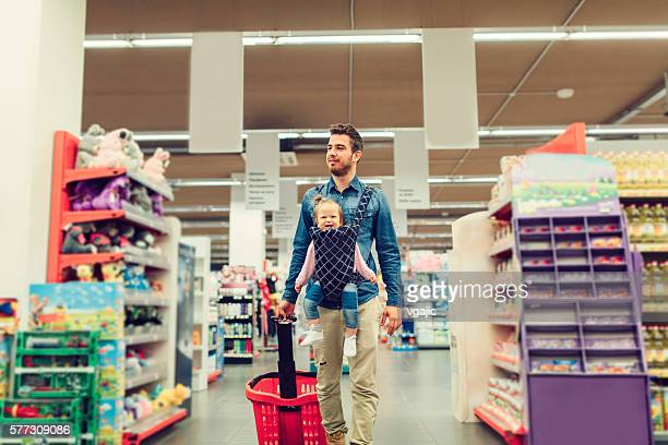 Father And His Baby Daughter Shopping In Local Supermarket.
