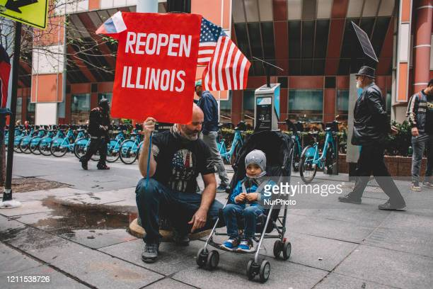 A father and his child attend the ReOpen Illinois protest in Chicago IL during protest restrictions instituted by the governor to curtail the spread...