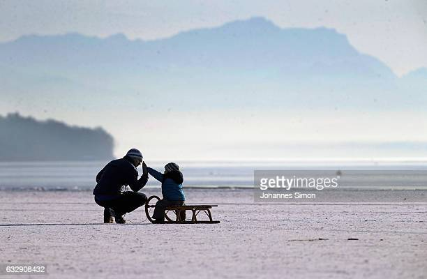 A father and his child enjoy walking on Lake Ammersee on January 28 2017 in Stegen am Ammersee Germany After an unusual cold winter period currently...