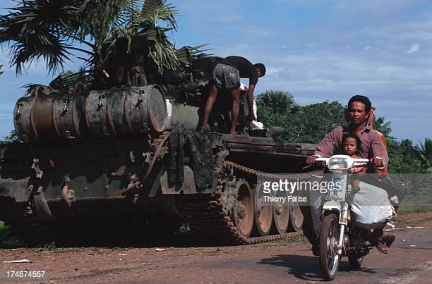 A father and his child pass a tank stopped on the road from Siem Reap to Sisophon during the coup d'etat