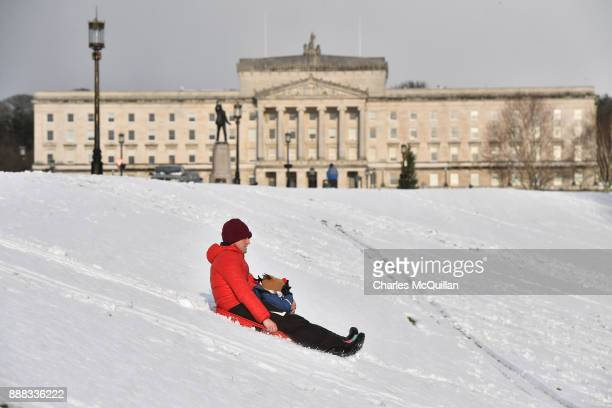 A father and his child play in the snow on their sled at Stormont on December 8 2017 in Belfast Northern Ireland The MET Office has issued a weather...