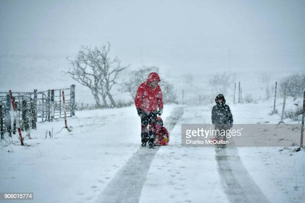 A father and his children make their way through the snow on January 17 2018 in Belfast Northern Ireland The Met Office has placed an amber weather...