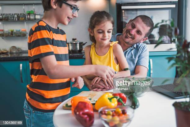 vader en zijn kinderen die salade samen op keuken thuis maken - alleenstaande vader stockfoto's en -beelden