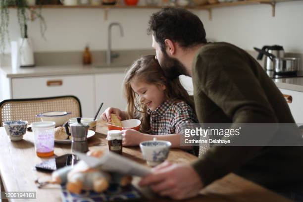a father and his daughter having their breakfast at home - frühstück stock-fotos und bilder