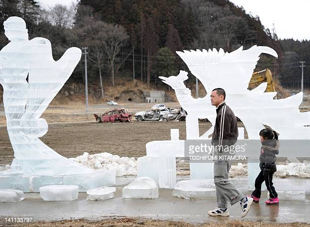 A father and his daughter walk beside an ice sculpture in Rikuzentakata city Iwate prefecture on March 11 201 2 Japan fell silent on Sunday to honour...