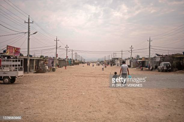 Father and his daughter walk down a central walkway at the Arbat refugee camp, 20Km east of Sulaimaniyah, Iraq's autonomous Kurdistan region's...