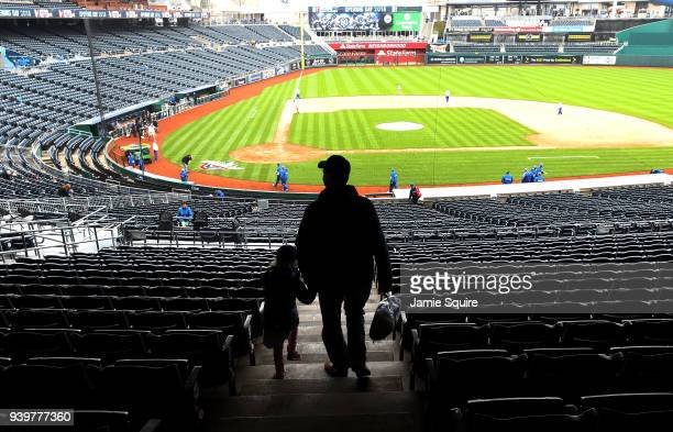 Father and his daughter walk through the stands toward the field as they arrive early on Opening Day ahead of the game between the Chicago White Sox...