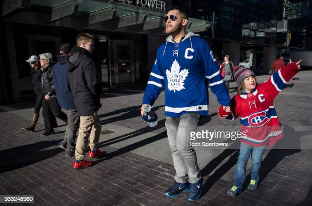 A father and his daughter wearing competing team jerseys take in the late day sun before the regular season NHL game between the Montreal Canadiens...