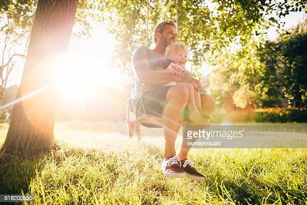 Father and his laughing son enjoy summer sunset on swing