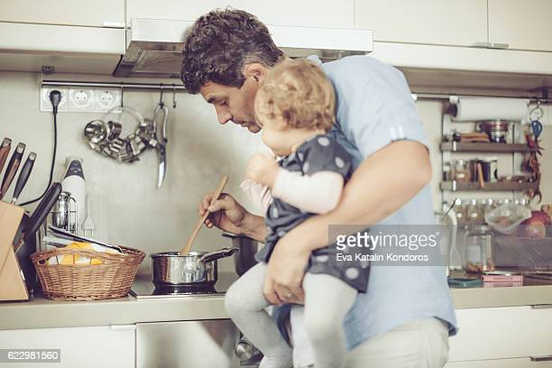 Father and his little daughter are cooking in the kitchen