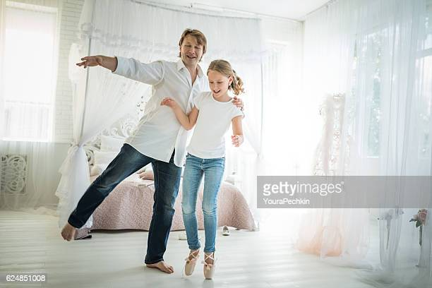 Father and his little daughter dancing at hotel room.