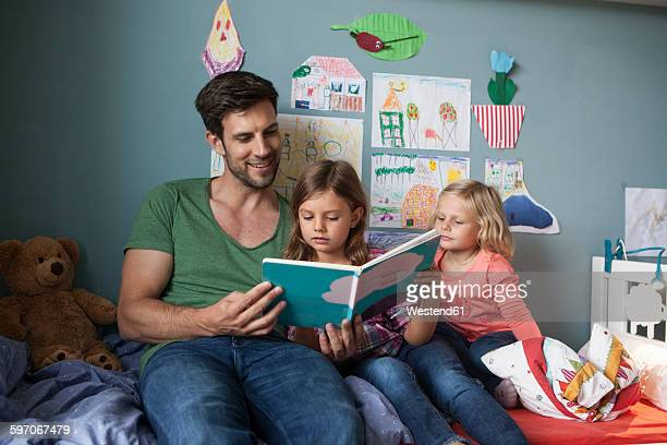 Father and his little daughters sitting together on bed in childrens room reading a book