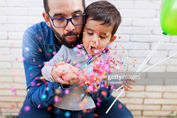 Father and his little son blowing confetti