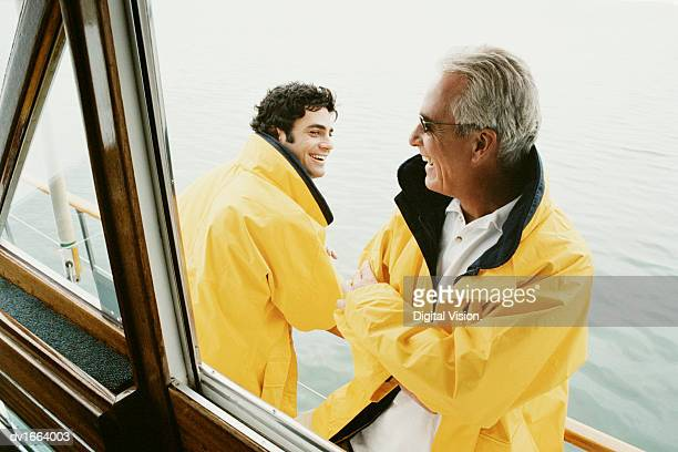 Father and His Mature Son Stand on the Deck of a Sailboat Laughing