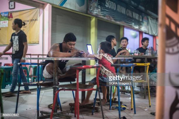 A 'WARKOP' IN SURABAYA EAST JAVA SURABAYA EAST JAVA INDONESIA A father and his son are pictured while enjoying wifi next to a Warkop during the night...
