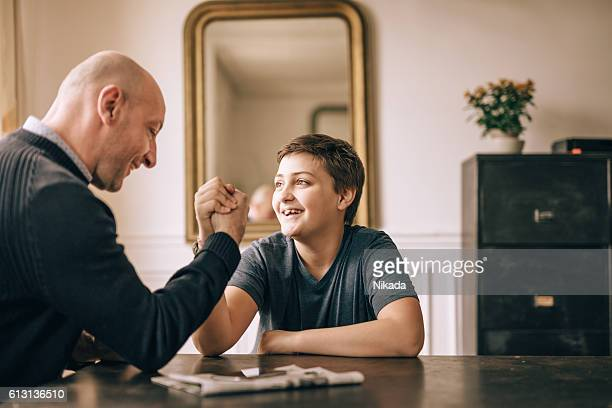 father and his son doing arm wrestling on table