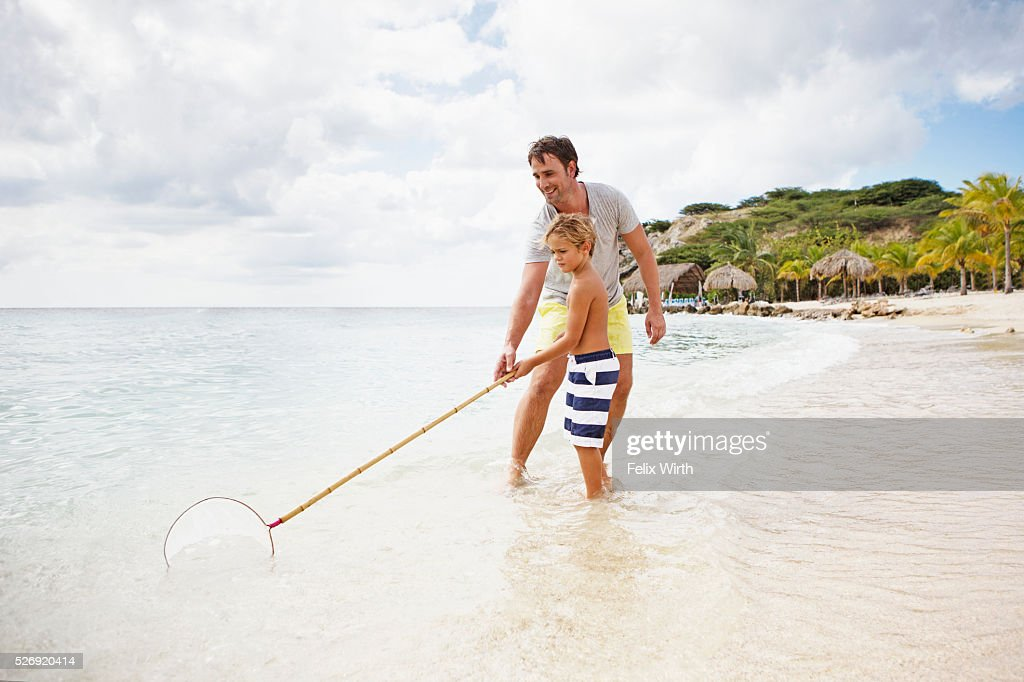 Father and his son (4-5) fishing on beach : Stock Photo