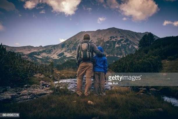 father and his son hiking in mountains at sunset - pirin national park stock pictures, royalty-free photos & images