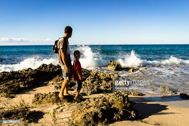 A father and his son in front of the sea, Saint-Louis, Marie-Galante, Guadeloupe, France