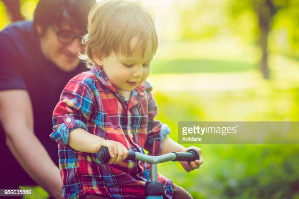 father and his son on a runbike in summer park - tricycle stock pictures, royalty-free photos & images