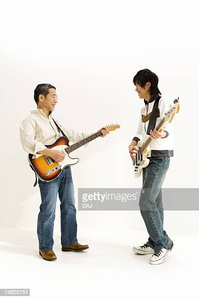 A Father and His Son Playing Guitars Together, Side View
