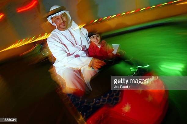 A father and his son ride on a bumper car ride November 3 2002 in Manama Bahrain The country is the home port for the United States Navy's 5th Fleet...
