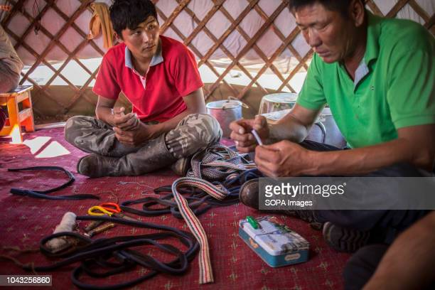 A father and his son sew homemade camels muzzles for their livestock near the town of Saikhan Ovoo in Dundgovi Province southern Mongolia
